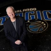 A picture of Pat Williams in front of the Orlando Magic logo